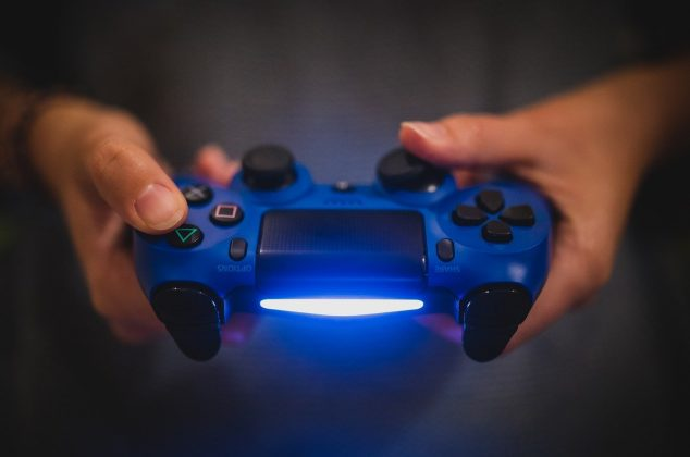 Hands holding a blue video game controller