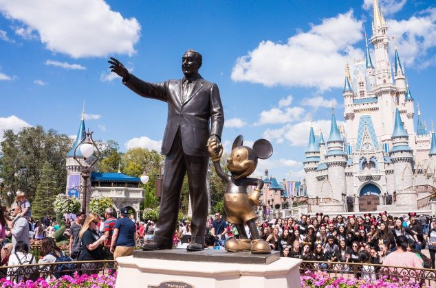 Walt Disney and Mickey Mouse statues at a Disney theme park