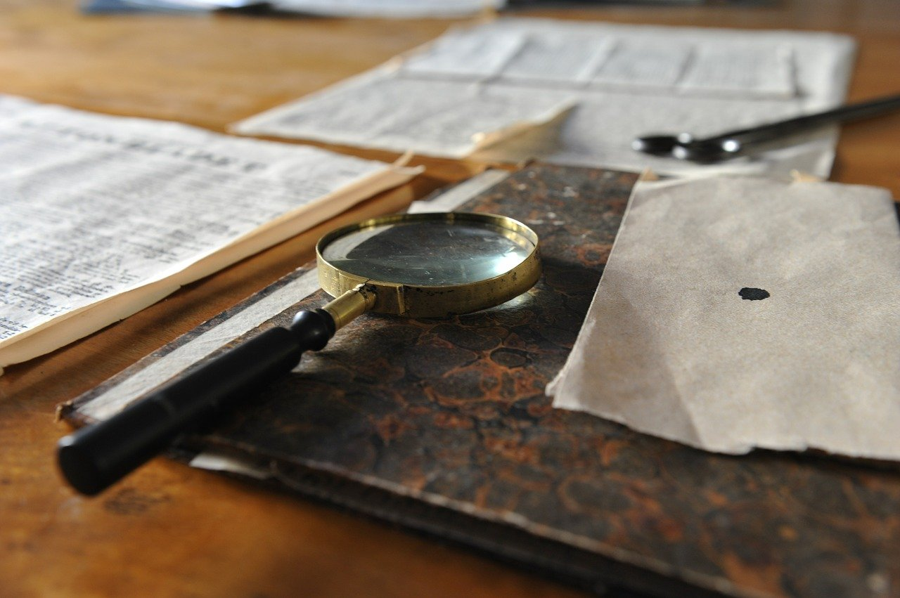 Detective's magnifying glass and documents resting on a desk