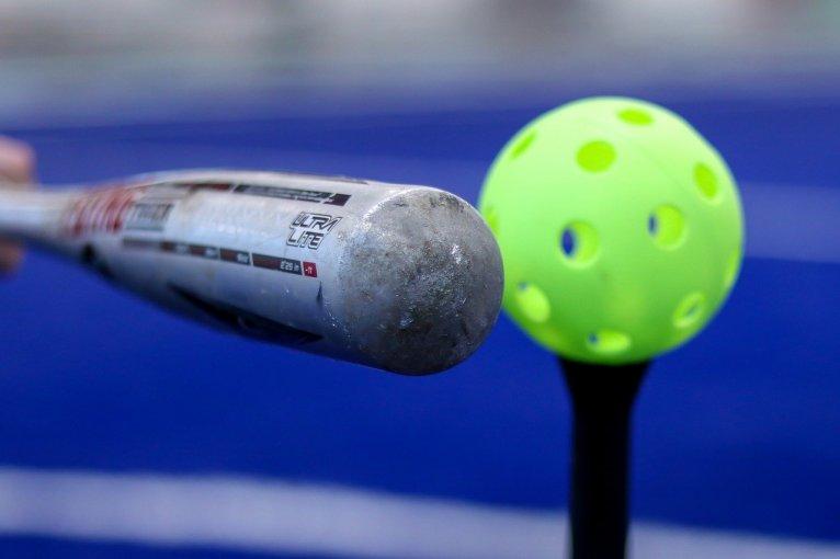 Silver bat hitting a green wiffle ball