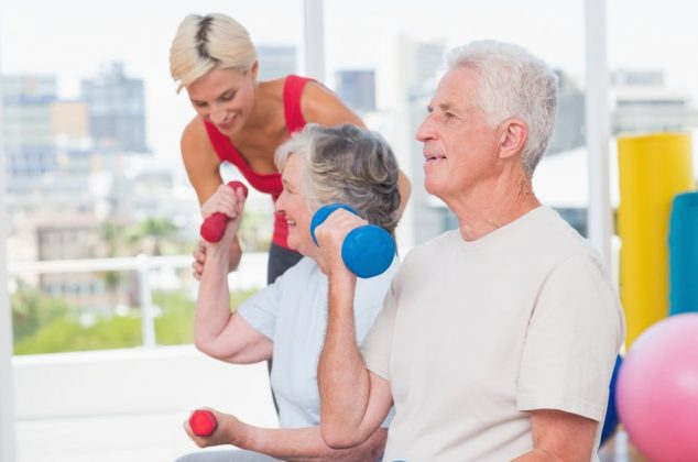 Two seniors and a trainer in a senior fitness class